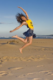 Girl with smily face top on jumping in the air