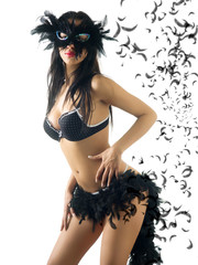 young cute brunette in lingerie with a black carnival mask