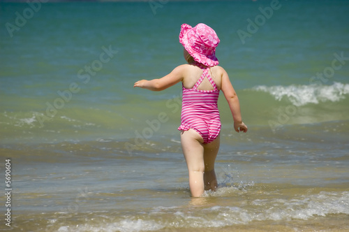 Little girl playing in waves at the beach