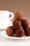 Gourmet chocolate truffles on a plate with a cup of coffee poster