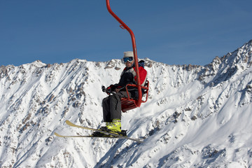 skier mowing up on ski lift under mountains