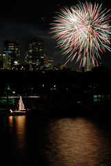 Fireworks over Boston. Colorful sailboat on Charles River.