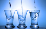 Clear liquid pour into three wineglasses toned in blue color poster