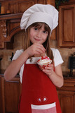 A cute young girl putting sprinkles on her cupcake poster