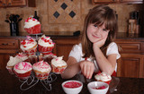 A cute young girl putting sprinkles on her cupcakes poster