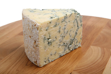 A wedge of mature Stilton cheese on a wooden board