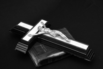 striking black and white image of an old crucifix laying on top