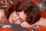 A beautiful red-haired woman taking a nap on her bed. poster