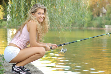 A beautiful young woman with a fishing pole