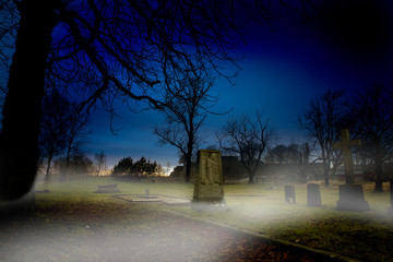 A spooky graveyard at sundown with mist