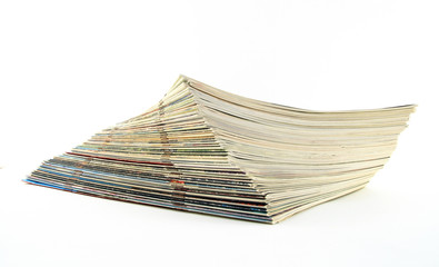 Pile of old weathered magazines on white background.