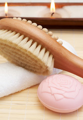 Relaxing spa scene with body brush massager, soap
