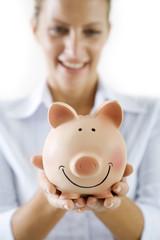 smiling female holding piggy-bank