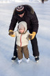 Winter recreation. Father and child skating on rink