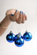Female hand with manicure and blue balls