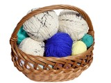 A color balls of yarn inside basket that is isolated  poster