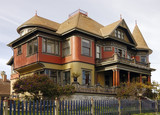 A large Victorian home with a lot of filigree on the facade poster