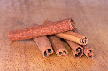 Dry cinnamon sticks on a textured wooden board