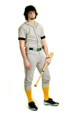A young male baseball player standing.