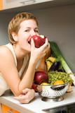 Fototapety Beautiful girl eating fresh fruits at the kitchen