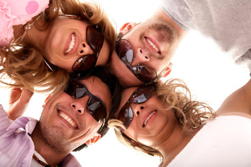 group of happy friends smiling and wearing sunglasses