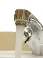 Close-up of head of mixer tap with water running