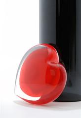 Red glass heart against wine bottle