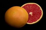 Halved ruby grapefruit on black background. poster