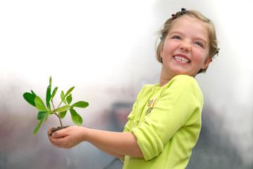 little girl holding small plant