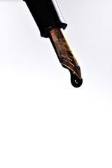 fountain pen spilling ink from golden tip