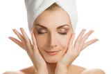 Fototapety Beautiful young woman massaging her face
