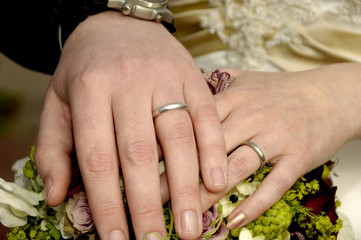 Two wedding hands with rings and flowers.