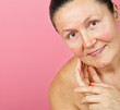 Older woman of great natural woman on a pink background
