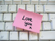 message love you post-it note on a computer keyboard