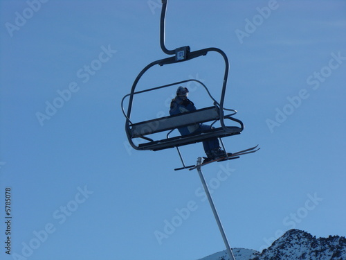 The mountain skier goes on the lift to mountains.