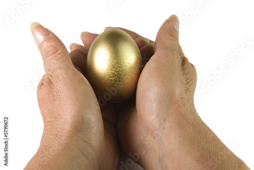 hands nesting a gold and shine egg