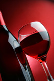 Still-life with bottle and glass of wine over red background-