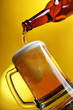 Pouring beer into mug over yellow background