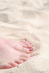 Woman's Feet Buried in White Sand