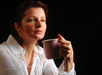 Beautiful woman in a melancholy mood over a cup of coffee