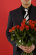 Smiling businessman with bouquet of roses in hands.