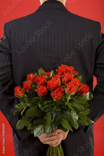 Businessman holding bouquet of roses behind his back.