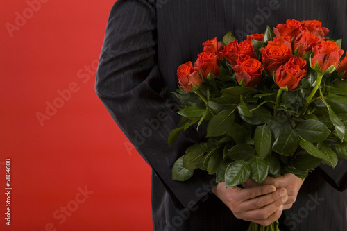 Businessman holding bouquet of roses behind his back