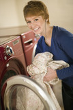 Woman taking laundry out of dryer poster