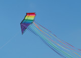 A string of colourful stunt kites with long tails poster
