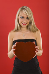 Beautiful woman in black dress, holding heart-shaped box