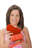 Happy young woman taking a plush heart out of a red gift box. poster