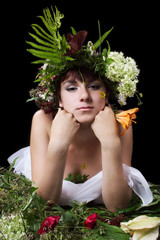 The girl in a wreath lays on a grass. Studio shoot