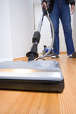 Cleaning chores: vacuuming hardwood floor. Wide angle. poster