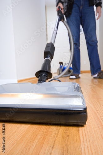 poster of Cleaning chores: vacuuming hardwood floor. Wide angle.